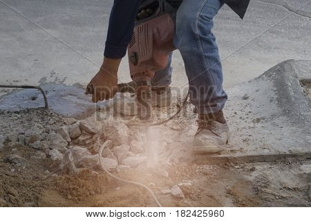 Construction workers are drilling cement with selective and soft focus.