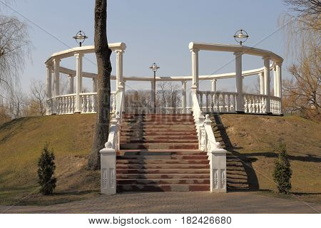 Openwork round arbor. White columns and stairs. Stands on a hill. Next tree.