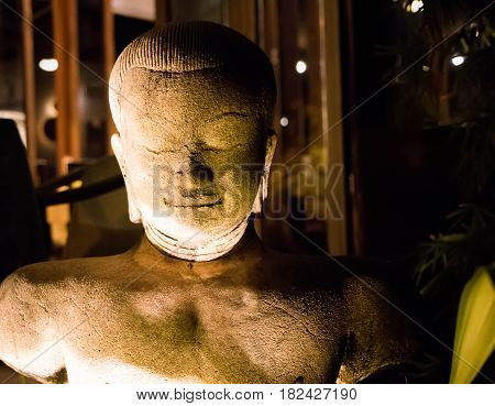 Relaxed stone Buddha statue at night lightened with warm lamps light. Buddhism religion concept small statue of smiling Buddha