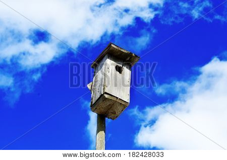 an old birdhouse made with his own hands on blue sky background