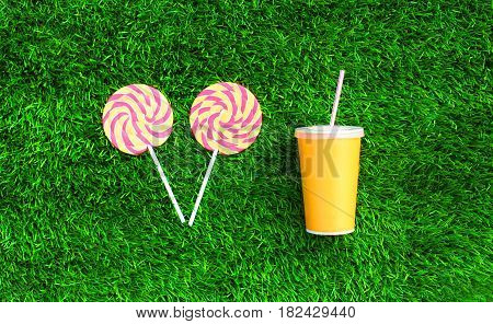 Yellow Cup Of Juice With Straw And Two Colorful Lollipop Caramel On Stick Over Green Textured Grass