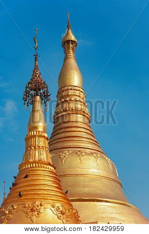 View of Myanmar temple spire. Popular place to visit at Yangon city tour - pagoda Shwedagon with Buddha scared relics. Famous travel destination in Asia. Traditional Burmese art and culture background
