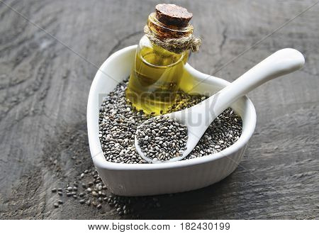 Chia seeds and chia oil in a white heart shaped bowl on old wooden background. Organic chia seed oil. Salvia hispanica seeds. Healthy food, superfood or bodycare concept. Selective focus.