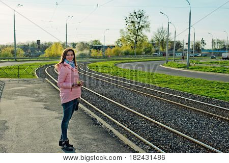 Young beautiful girl is waiting for a tram at the tram stop. Urban backgrounds.