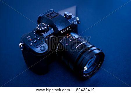 PARIS FRANCE - APR 9 2017: Blue tone view detail of the Panasonic Lumix DMC-GH5 - and Leica Vario-Elmarit 12-60 Micro Four Thirds System digital still and video camera with 4K 10 bit Video recording internal capability.