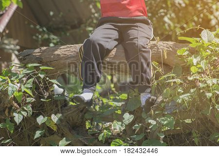 Sitting on wooden legs dangling with selective and soft focus.