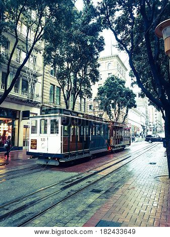 San Francisco, USA - October 28, 2016; In the city on wet rainy day tram runs along San Francisco street lined with buildings and trees in old-fashioned effect image.