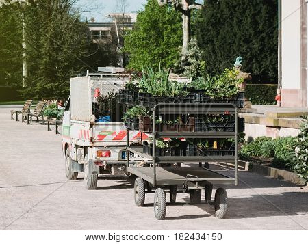 STRASBOURG FRANCE - APR 12 2016: Rear view of gardener van with carriage trailer transporting toward destination new fresh flowers tree and bushes for the green spring park