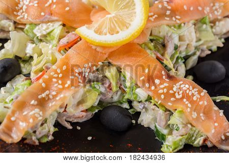 Salad with salmon vegetables lemon and black olives on black plate. Close up image.