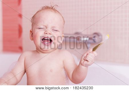 Crying Baby Boy Getting Teeth Washed With Toothbrush. Infant Kid With A Toothbrush In A Tub