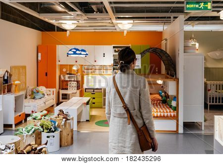 PARIS FRANCE - APR 10 2017: Woman choosing kids furniture in IKEA Shopping furniture store in Paris France. Being founded in Sweden in 1943 IKEA is the world's largest furniture retailer.