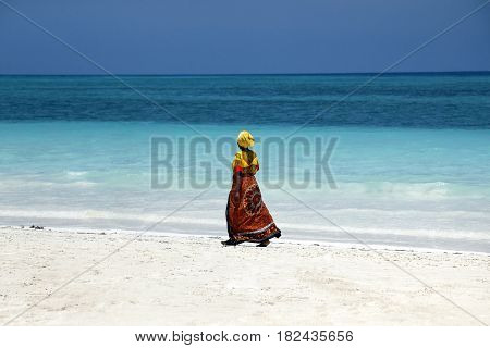Zanzibar Tanzania - January 7 2016: An African woman in traditional dress walks down the beach. Zanzibar Tanzania