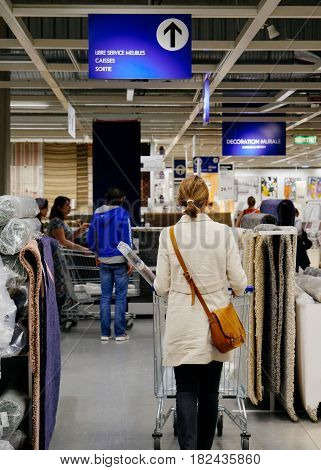 PARIS FRANCE - APR 10 2017: Rear view of woman choosing carpets and other furniture in IKEA Shopping furniture store in Paris France. Being founded in Sweden in 1943 IKEA is the world's largest furniture retailer.