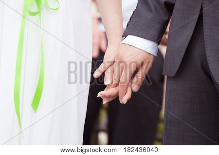 Bride and groom holding hands, symbol of marriage, love symbol, wedding ceremony hand detail, love concept