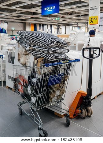 PARIS FRANCE - APR 10 2017: Caddy full with merchandise and household goods inside IKEA Shopping furniture store in Paris France. Being founded in Sweden in 1943 IKEA is the world's largest furniture retailer.