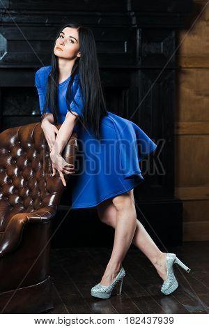 Girl In Blue Dress Near The Armchair.
