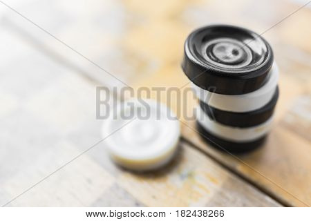 White and black checkers standing on top of each other on a light brown old shabby chessboard.Winning strategy concept