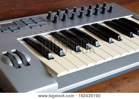 Electronic synthesizer keyboard with control wheels and knobs in silver plastic body on wooden background side view closeup