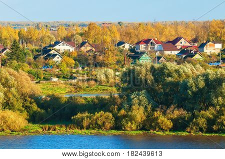 Autumn landscape - birds eye view of small autumn village near the river in the autumn forest at sunset. Wooden houses between the yellowed autumn trees -autumn background. Colorful autumn landscape