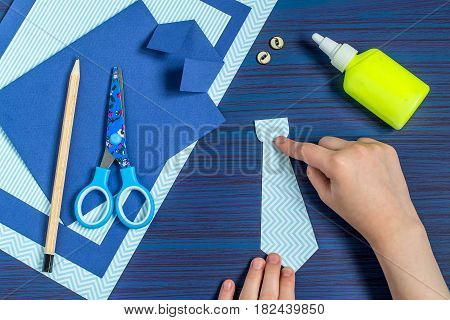 Making greeting card for Father's Day. Children's art project. DIY concept. Step-by-step photo instruction. Step 7. Child glues together parts of a tie