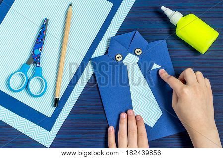 Making greeting card for Father's Day. Children's art project. DIY concept. Step-by-step photo instruction. Step 9. Child glues pocket and buttons
