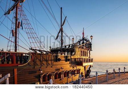A stern of a touristic pirate ship at the pier (molo) in Sopot, Poland, in sunrise light