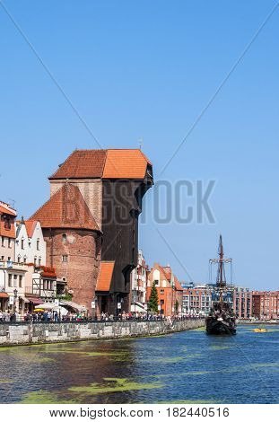 GDANSK, POLAND - AUGUST 27, 2016: Old city with medieval wooden port crane the oldest in Europe Motlava river tourist pirate ship boat and crowd of people walking along the quay