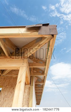 Corner of house with eaves wooden beams and roof asphalt shingles