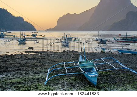 An boat under Palms on Tropical island, bis Rock island on background, cloudy sky El Nido, Palawan, Philippines, Asia