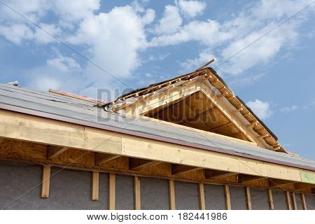 New frame house under construction. Roof with asphalt shingles chimney and insulation material in attic