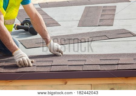 Roofer builder worker installing Asphalt Shingles or Bitumen Tiles on a new house under construction