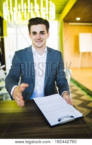 Handsome Buisnessman With Open Hand Ready For Handshake Before Deal At His Workplace In Office