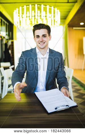 Handsome Buisnessman With Open Hand Ready For Handshake Before Sign Of Contract At His Workplace In