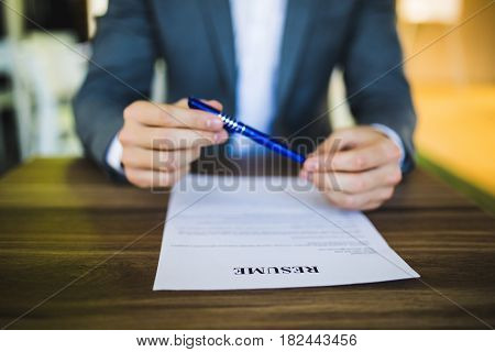 Businessman Or Job Seeker Review His Resume On His Desk Before Sending To Find A New Job With Pen