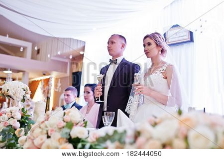 Wedding Couple With Champagne Glasses At Table On Restaurant With They Friends.