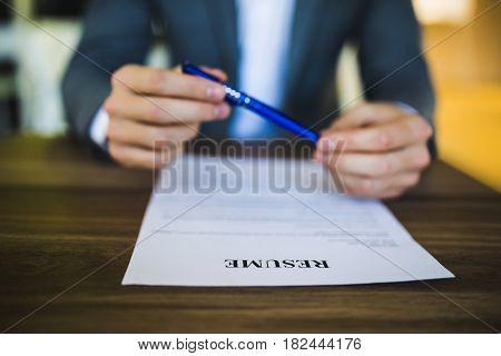 Close-up Of Person Hand Holding Curriculum Vitae, Resume On Table