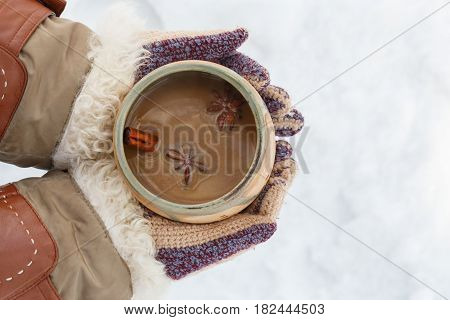 Female Hands In Knitted Grey Mittens Hold White Cup Of Spicy Coffee With Anisetree Star.