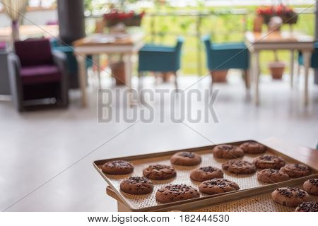 Chocolate Cookies With Crackles And Chocolate Chips Lay At Metal Tray At The Background Of Cafe Inte