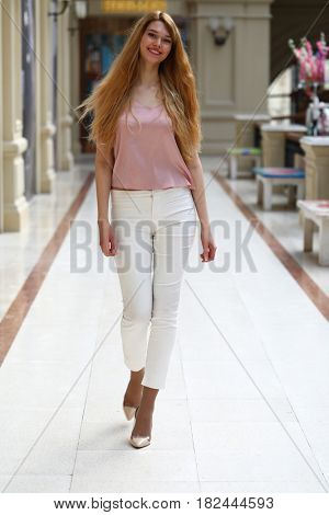 Full length portrait, young beautiful blonde woman in white pants and pink blouse walking in the shop