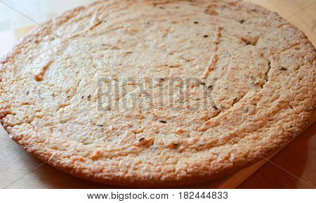 Round flat bread with caraway seeds on a wooden board