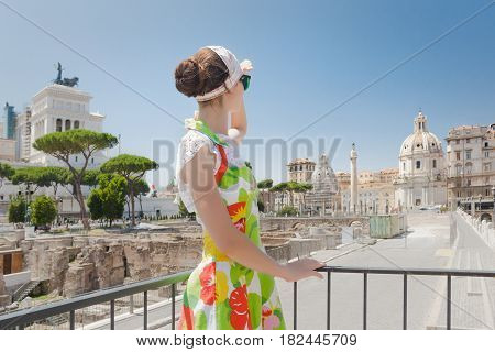Back view of tourist girl is looking ahead on Roman ruins