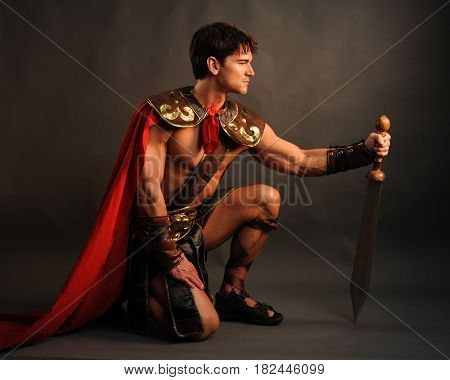 The sexy medieval gladiator is crouched down.