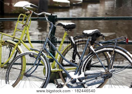 Bikes parked outside in the winter snow in Amsterdam, Netherlands.