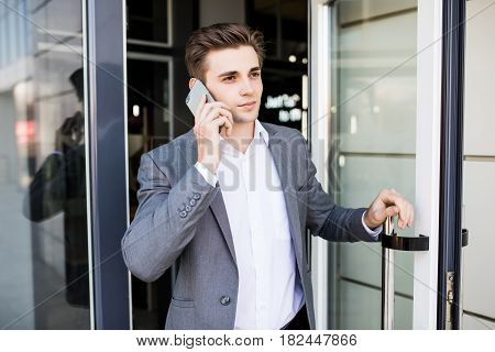 Young Business Man Holding The Office Door And Get Outside White Speak On Phone