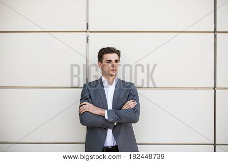 Young Businessman Standing With His Arms Folded With Office Buildings In Background