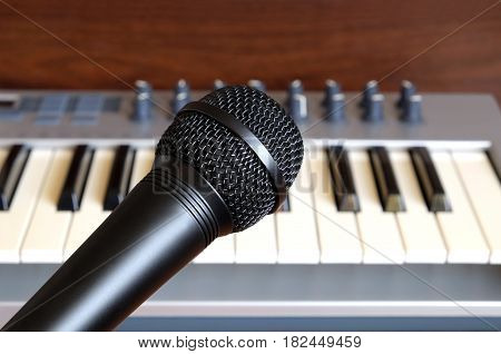 Black vocal microphone close up against electronic synthesizer keyboard with many control knobs in silver plastic body as background