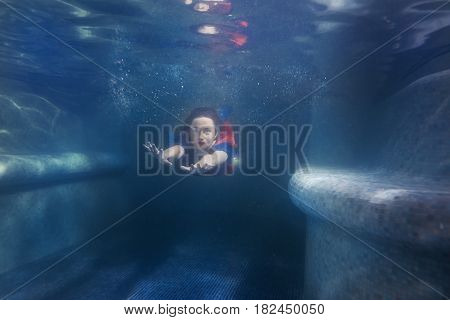 Woman swims under the water in the pool like a mermaid.