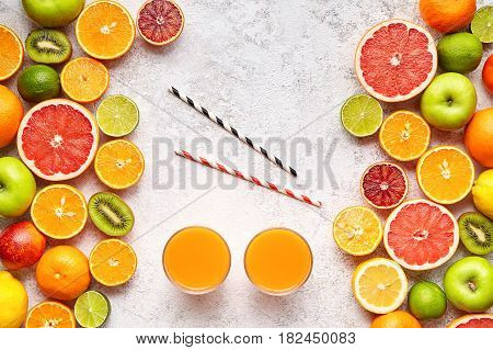 Smoothie or fresh juice vitamin drink in citrus fruits background flat lay, healthy lifestyle vegetarian organic antioxidant detox diet beverage. Tropical summer assortment grapefruit, orange, apple