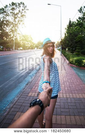 Beauty woman in blue hat holding man by hand and going around the Alanya city in Turkey