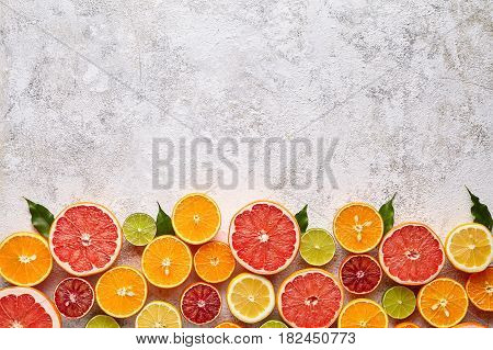 Citrus fruits vegan mix flat lay on white background, healthy vegetarian organic food, antioxidant detox diet. Tropical summer mix grapefruit, orange, apple, mandarin, sliced kiwi fruit, lime
